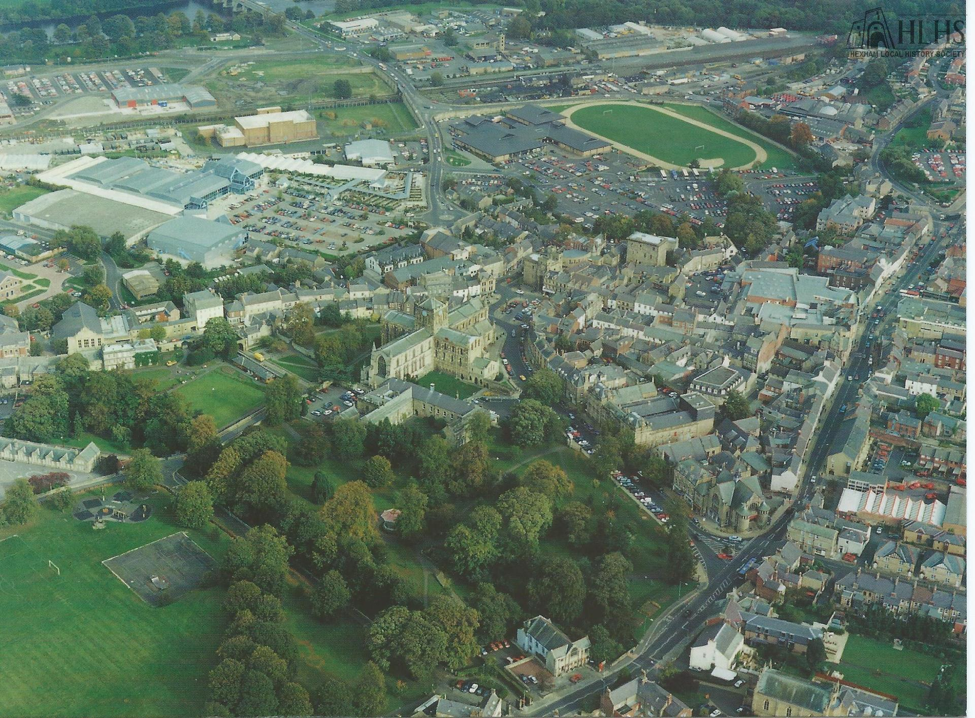 1995: Hexham, aerial view looking NE, centred on the Abbey, Battle Hill, Priestpopple, Beaumont Street with Robbs Tynedale Retail Park and railway in distance